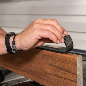 Measure and cut a piece of wall flash the width of the deck or the width of the house.