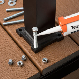 For a flush mount post, install the decking first. Install the post applying a small bead of caulk to the threads.