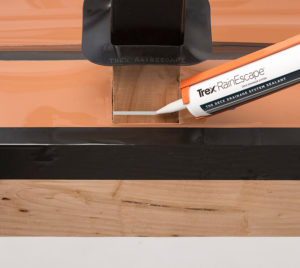 "If using a post sleeve, slide the sleeve down 2""-3"" from the top of the joists and run a bead of caulk around the base of the post."