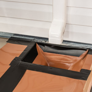 When installing a second-story downspout that dumps into the RainEscape system, install the surrounding trough and then tape all the joists and seams making a watertight seal.