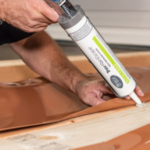 Lift the trough and run a bead of caulk underneath.
